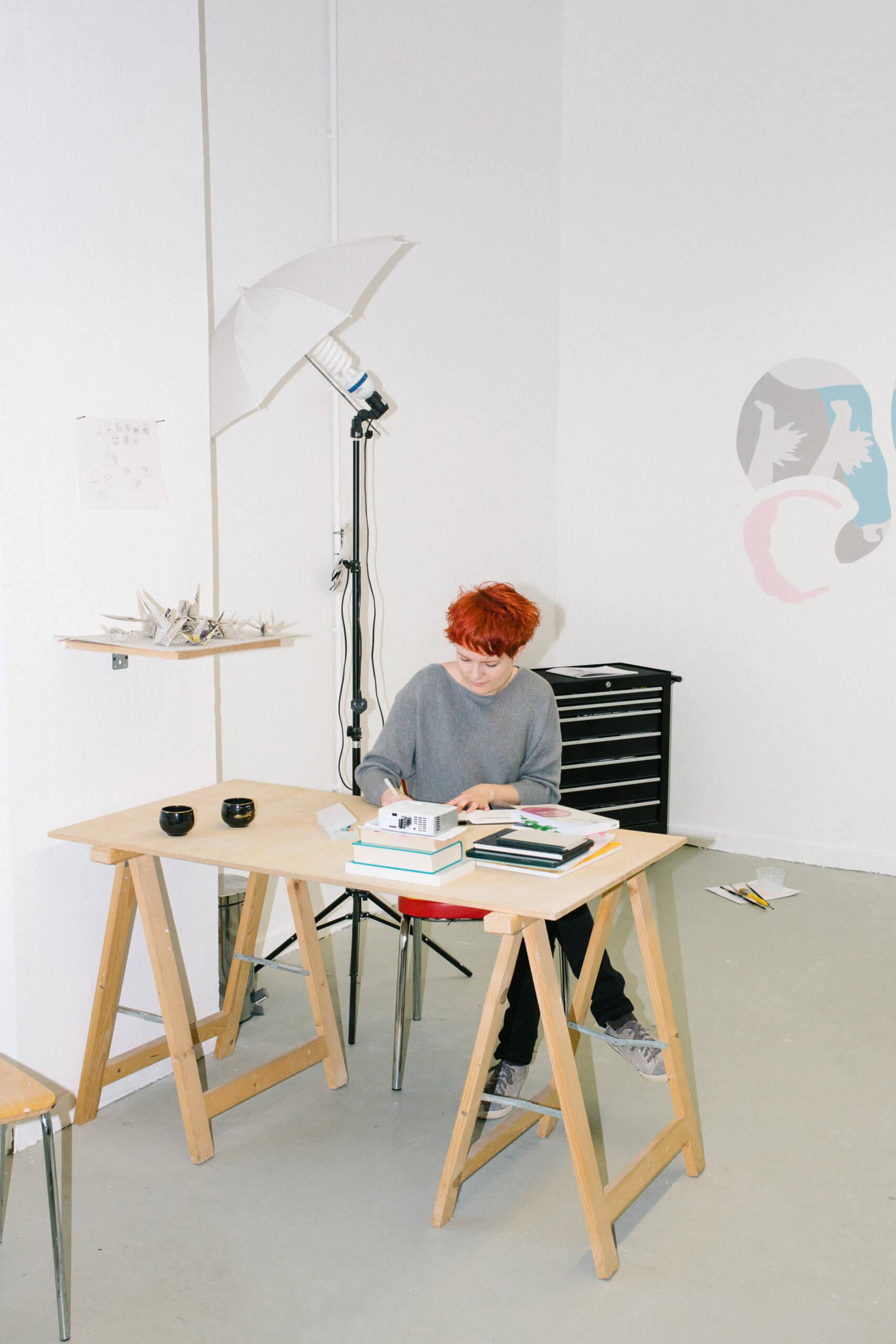Auf dem Bild arbeitet Stefanie Gerstmayr an ihrem Schriebtisch. Sie schreibt per hand auf einen Zettel. Im Hinterghurnd ist eine Wandarbeit von ihr zu sehen und links tehat en Fotoblitzlicht auf einem Stativ.