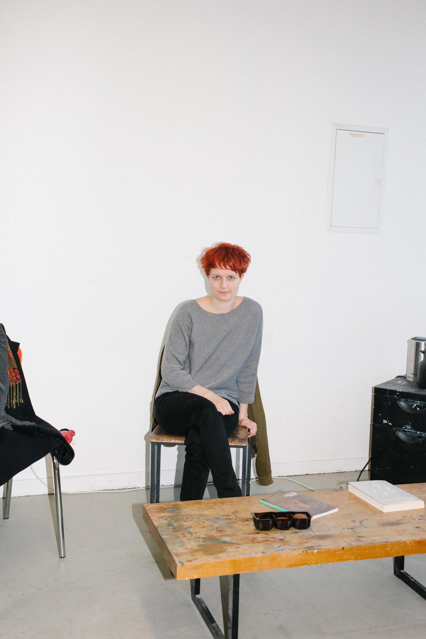 Auf dem Bild ist die Künstlerin Stefanie Gerstmayr sitzend in Frontalansicht zu sehen. Se lächelt in die Kamera und im unteren Bildran ist ihr Schreibtisch