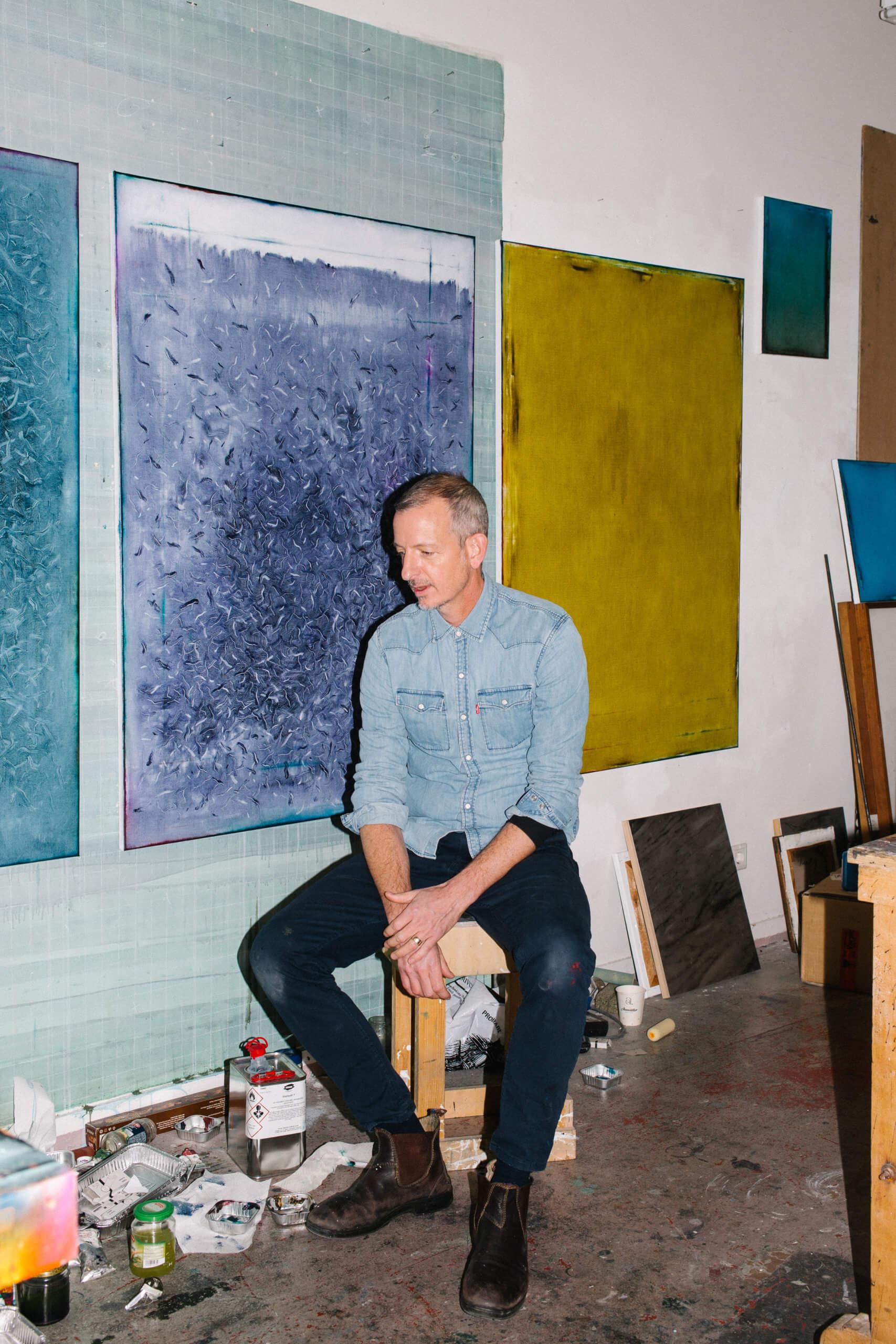 Duncan Swann sitz auf einem Kocker in seinem Atelier, vor abstrakten Acrygemäöden, die an der Wand hängen.