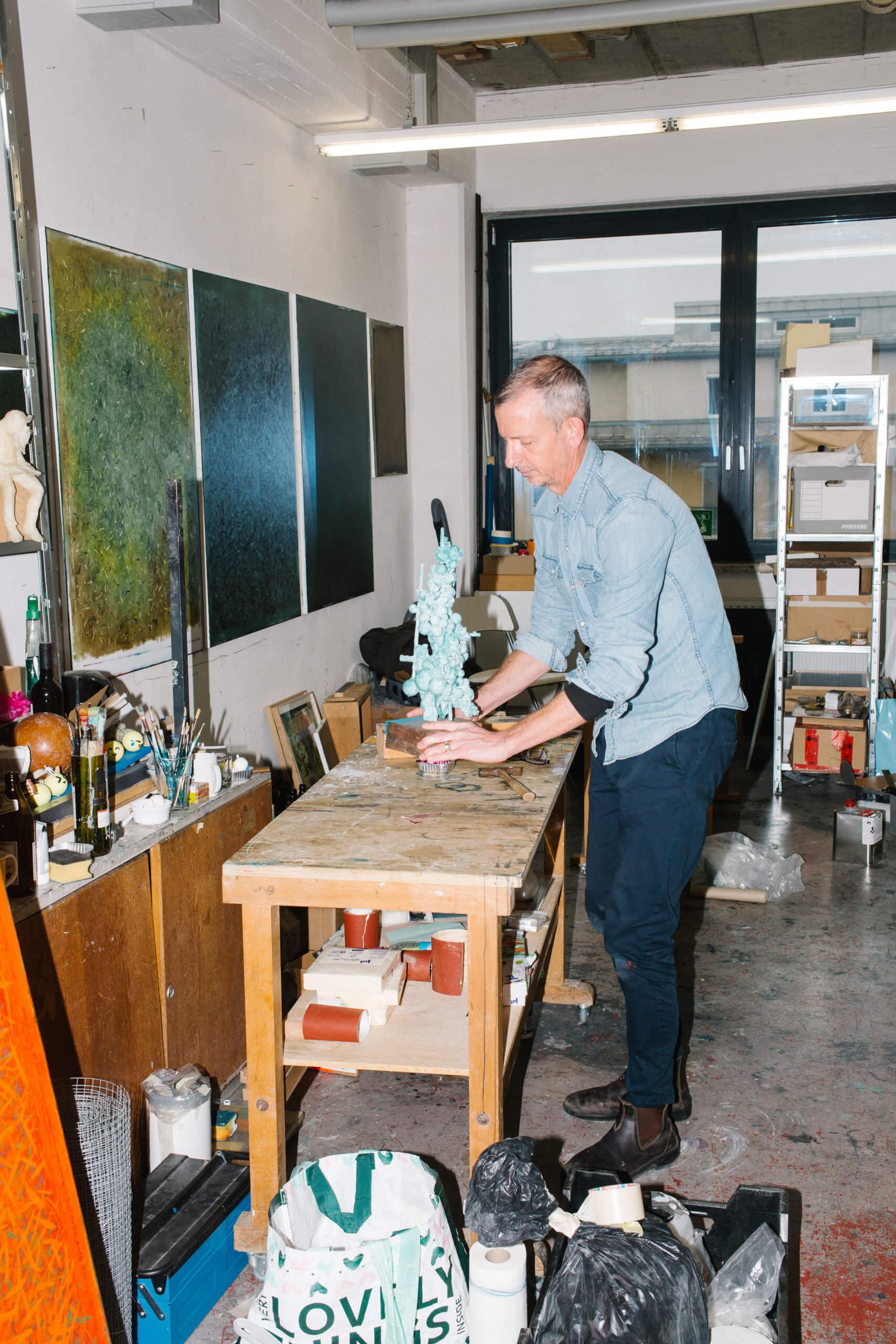Der Künstler Duncan Swann steht in seinem Atelier vor einem Tisch und bearbeitet eine Skulptur