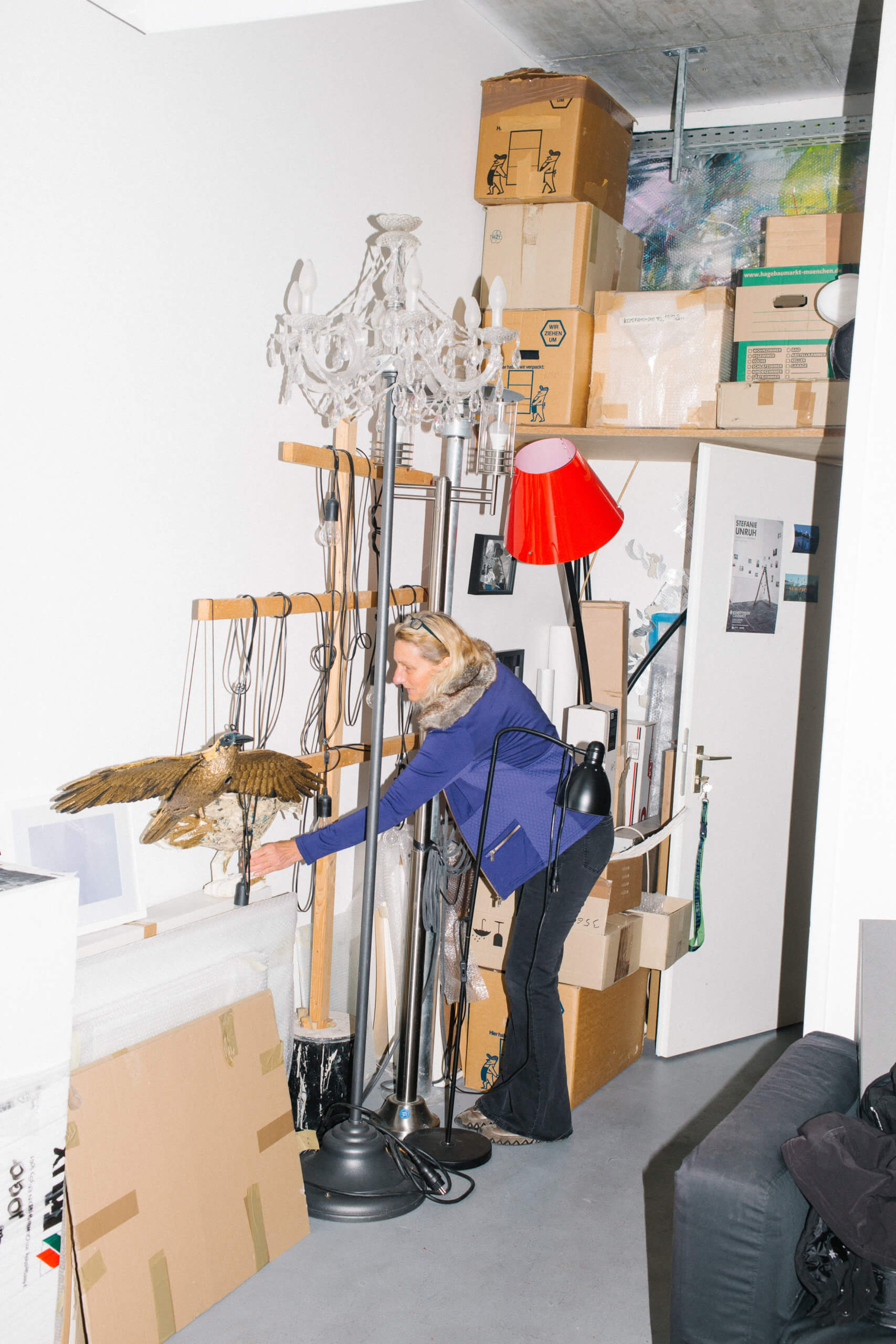 Es wird die Künstlerin im Halbprofil, stehend in ihrem Atelier gezeigt. Sie hält ien Platsiokvogel in der Hand, welcher an einer Stange an der Wand hängt.