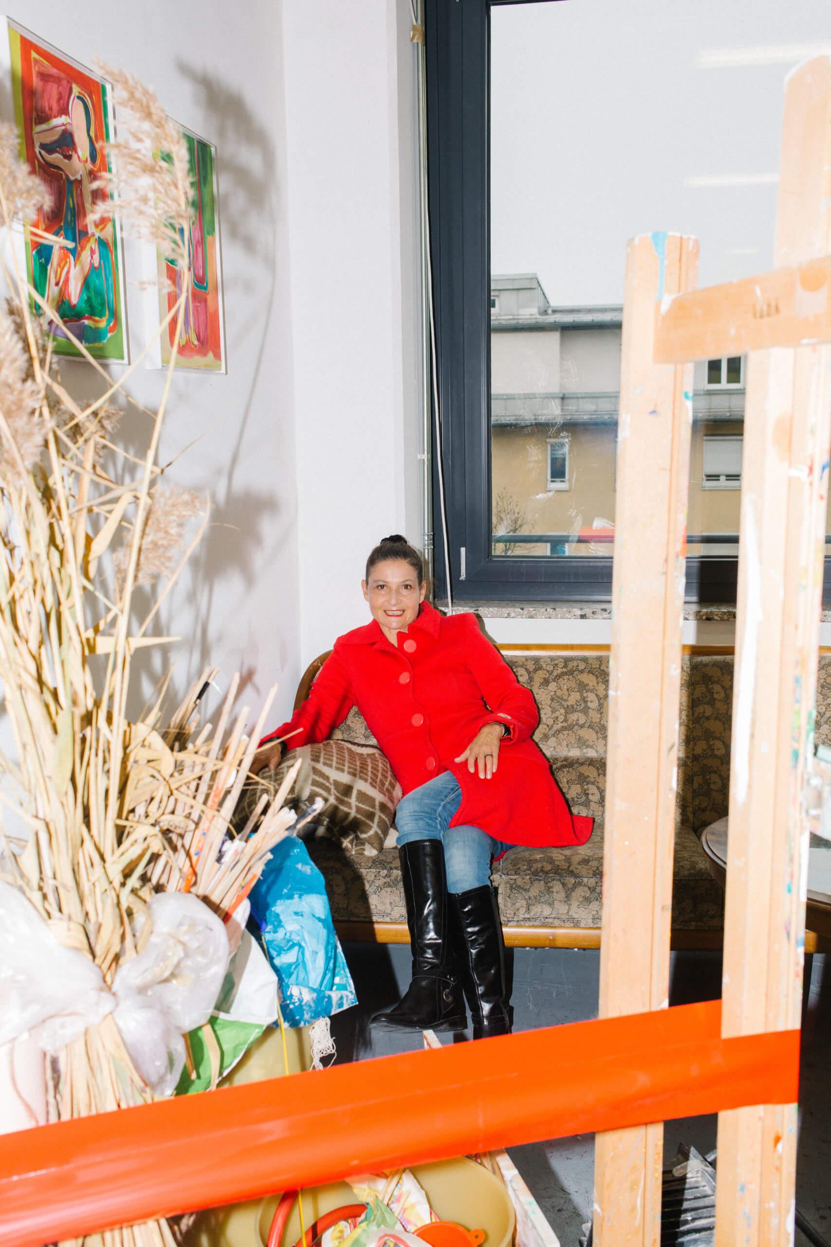 Porträt der Künstlerin in ihrem Atelier. Sie sitzt mit roten Mantel auf ihrer Couch. Im Vordergrund sind Teile ihrer Installation