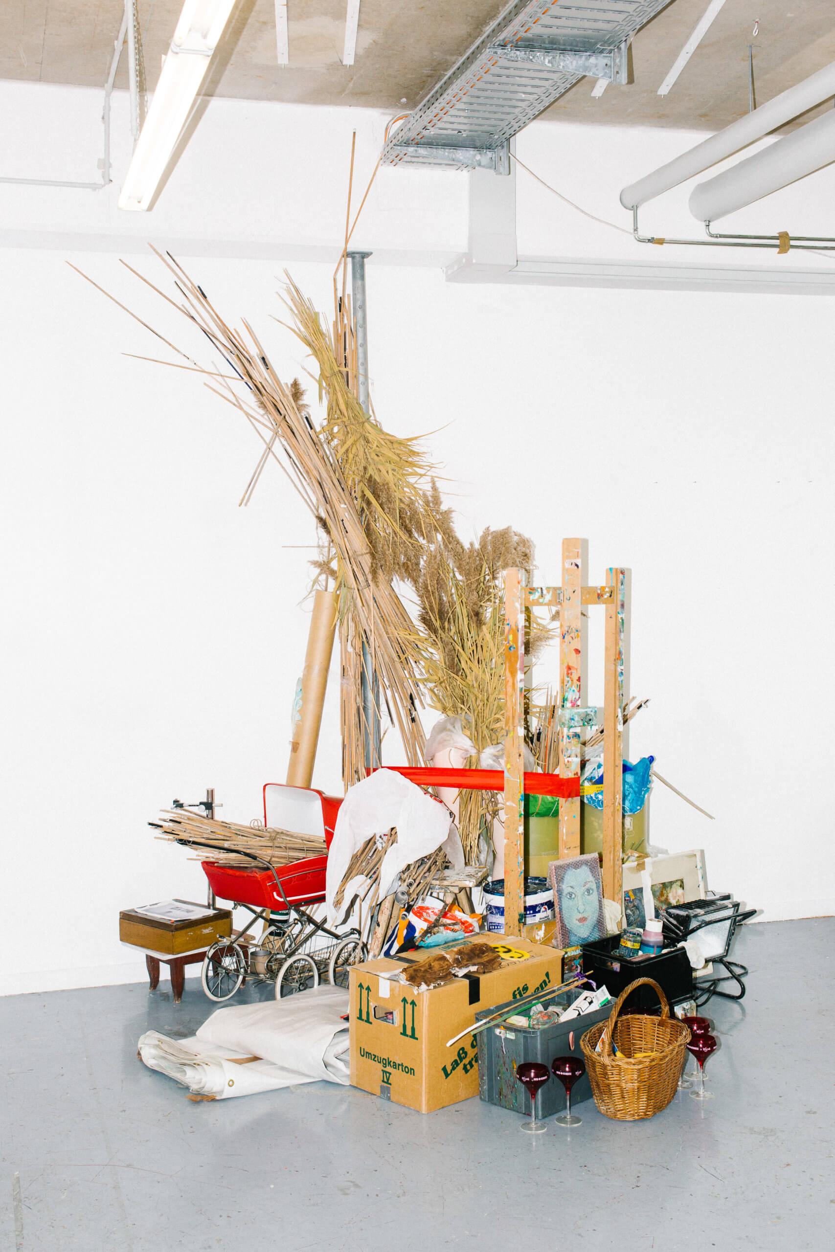 """Die Installation """"Alle meine Werkzeuge"""", aus verschiednen Materialien zusammengestetzt. Eine Pyramide aus Stroh, Holz, Plasik dosen und Kartons. Sie ist 4 meter hoch, 5 meter breit und 3,50 tief und stammt von 2020."""