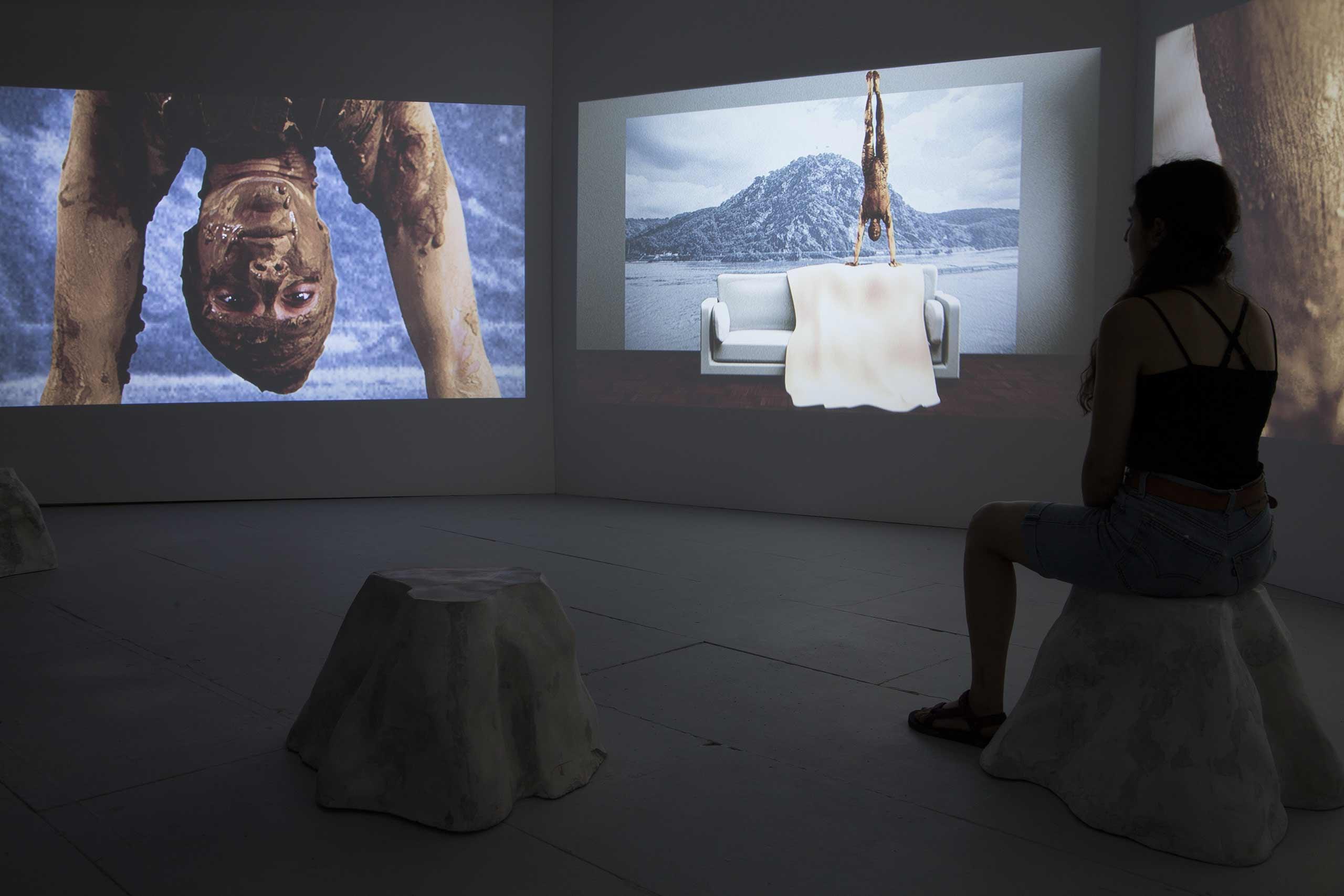 """Das BIld zeigt einen Ausschnitt der drei-Kanal-Installation """"Bite the sunset"""" von Stefanie Gerstmayr da. dein Frau in Rückansicht, schaut sich sitzend zwei videos an. auf dem einen springt eine Frau kopfüber ins Wasser, während auf dem anderen eine Insel zu sehen ist."""