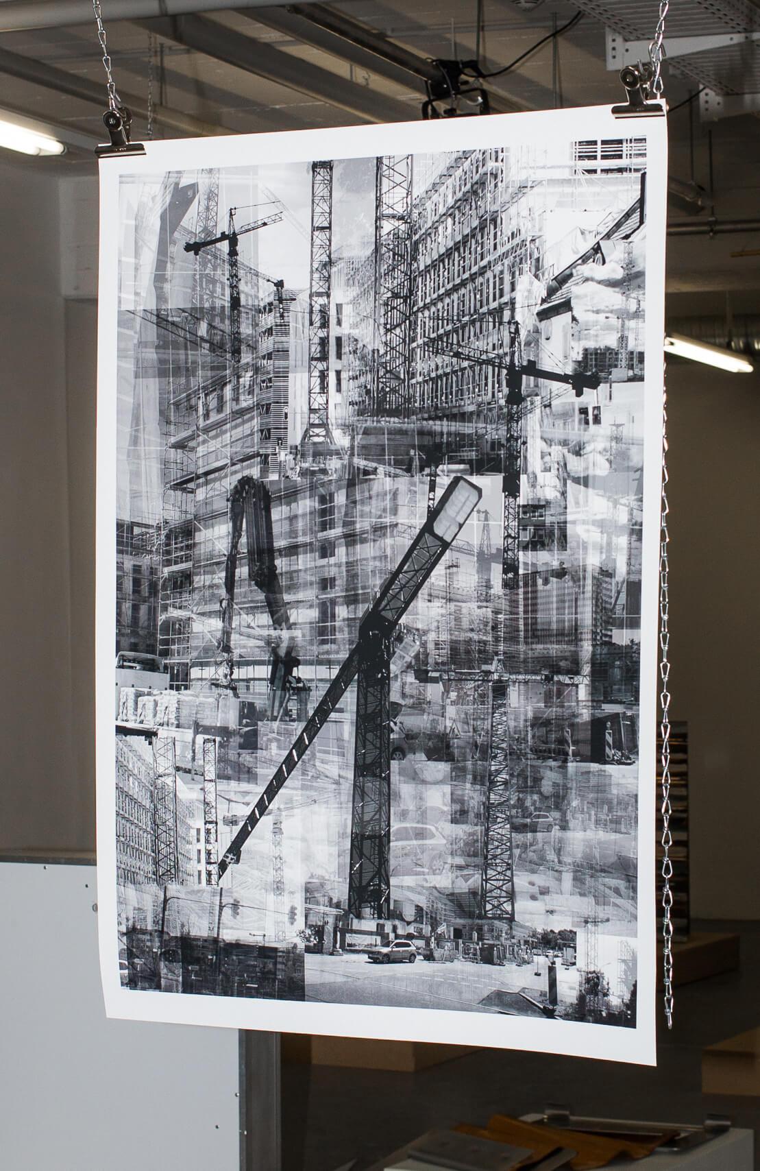 """Das Bild zeigt die Fotoarbeit """"Buastelle"""" von 2020. DIe Schwarzweiß Fotografie hängt an zwei Ketten im Raum. Die Fotografie selber ist eine Collage von unterschiedlichen Baustellenbildern von Hochhäuser, Kränen und Gerüsten."""