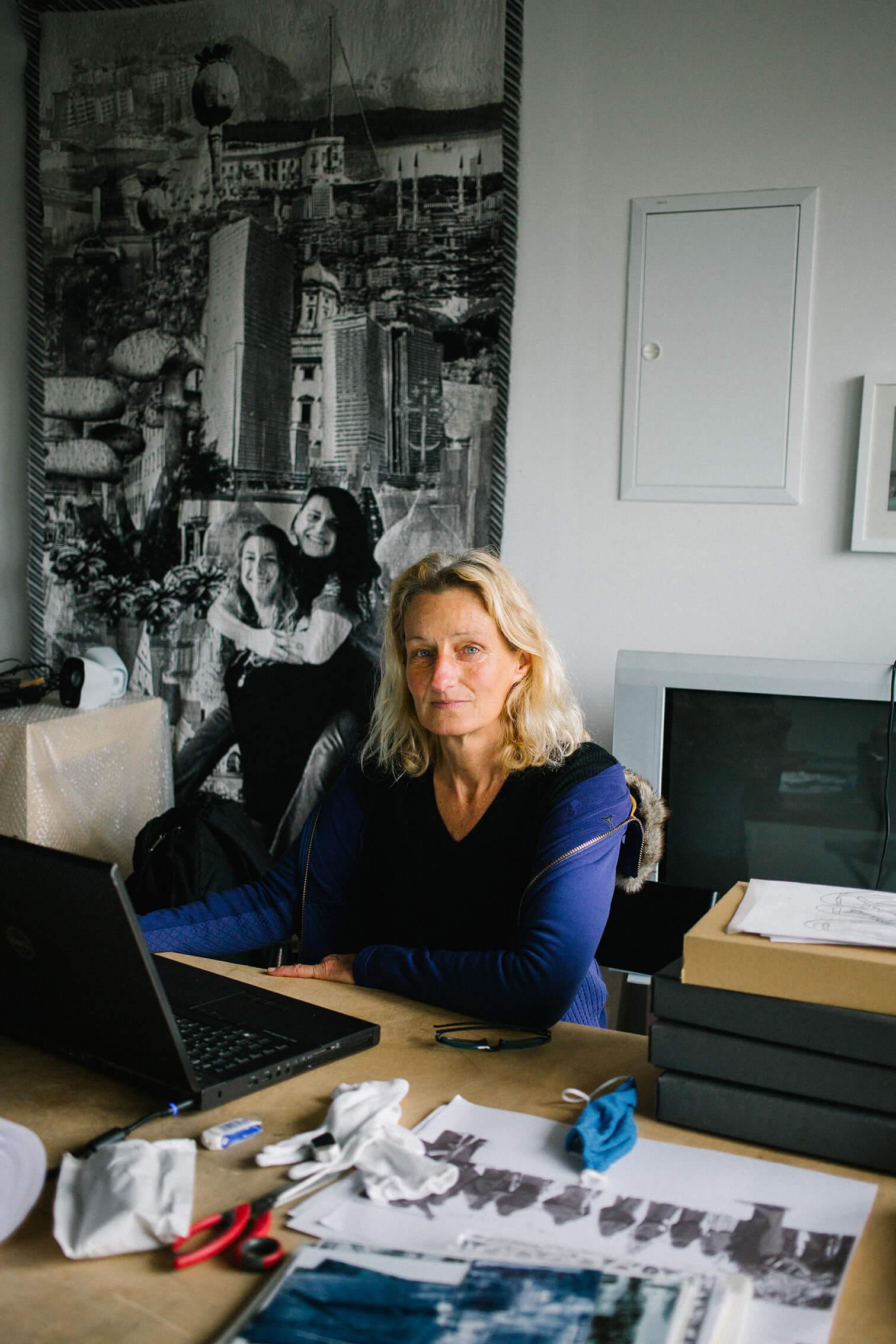 Das Bild zeigt die Künstlerin Stefanie Unruh sitzen an ihrem Schreibtisch, im Atelier. Hinter ihr hängt eine schwarz weiß arbeit von ihr. Diese zeigt eine colgae von verschiednene Bildern, zwei junge Frauen die sichHuckepack nehmen, Pilze und Industrielandschaften.