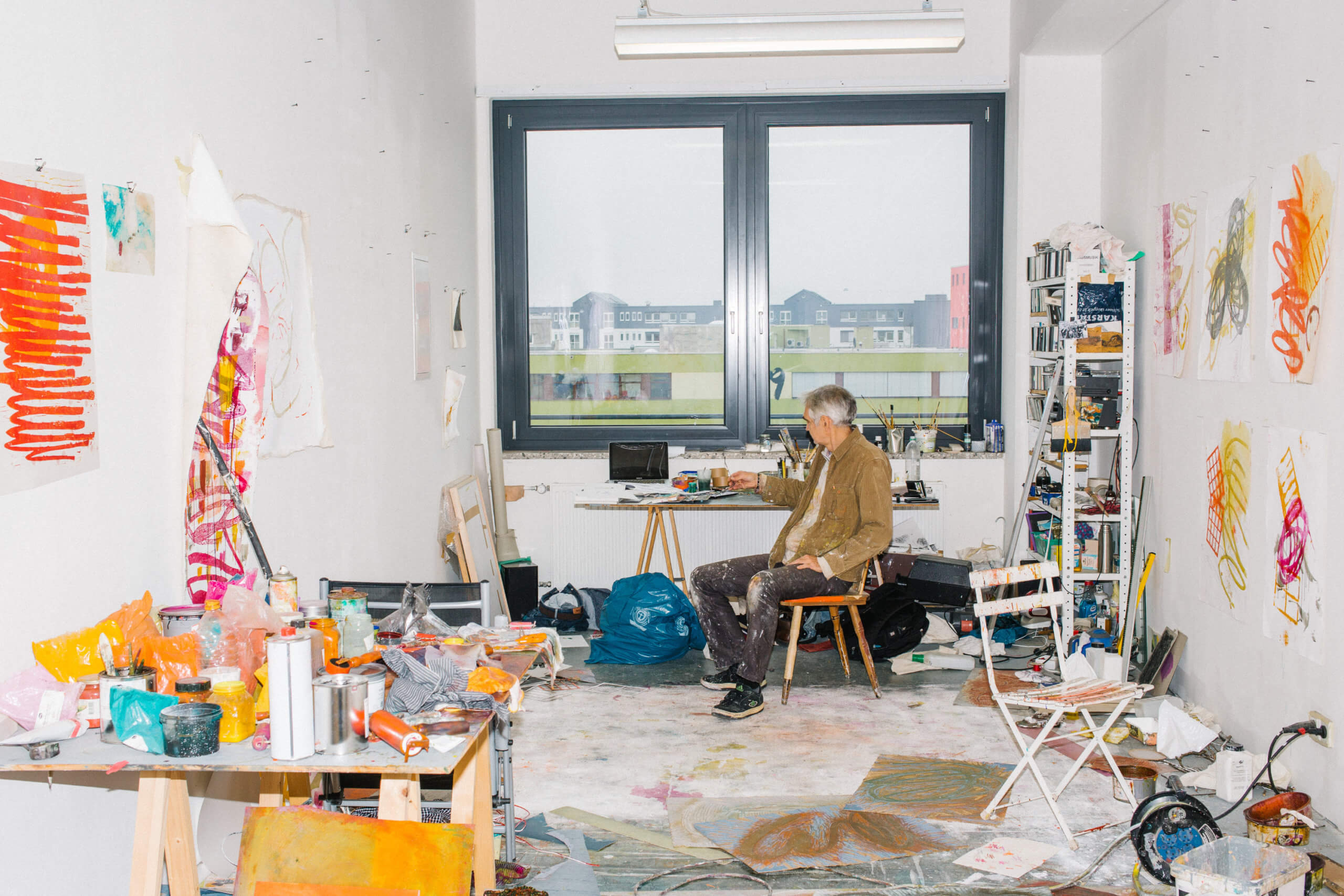 Man sieht das Atelier von Jess Walter. Der Künstler sitz mittig an seinem Tisch, vor dem Fenster.