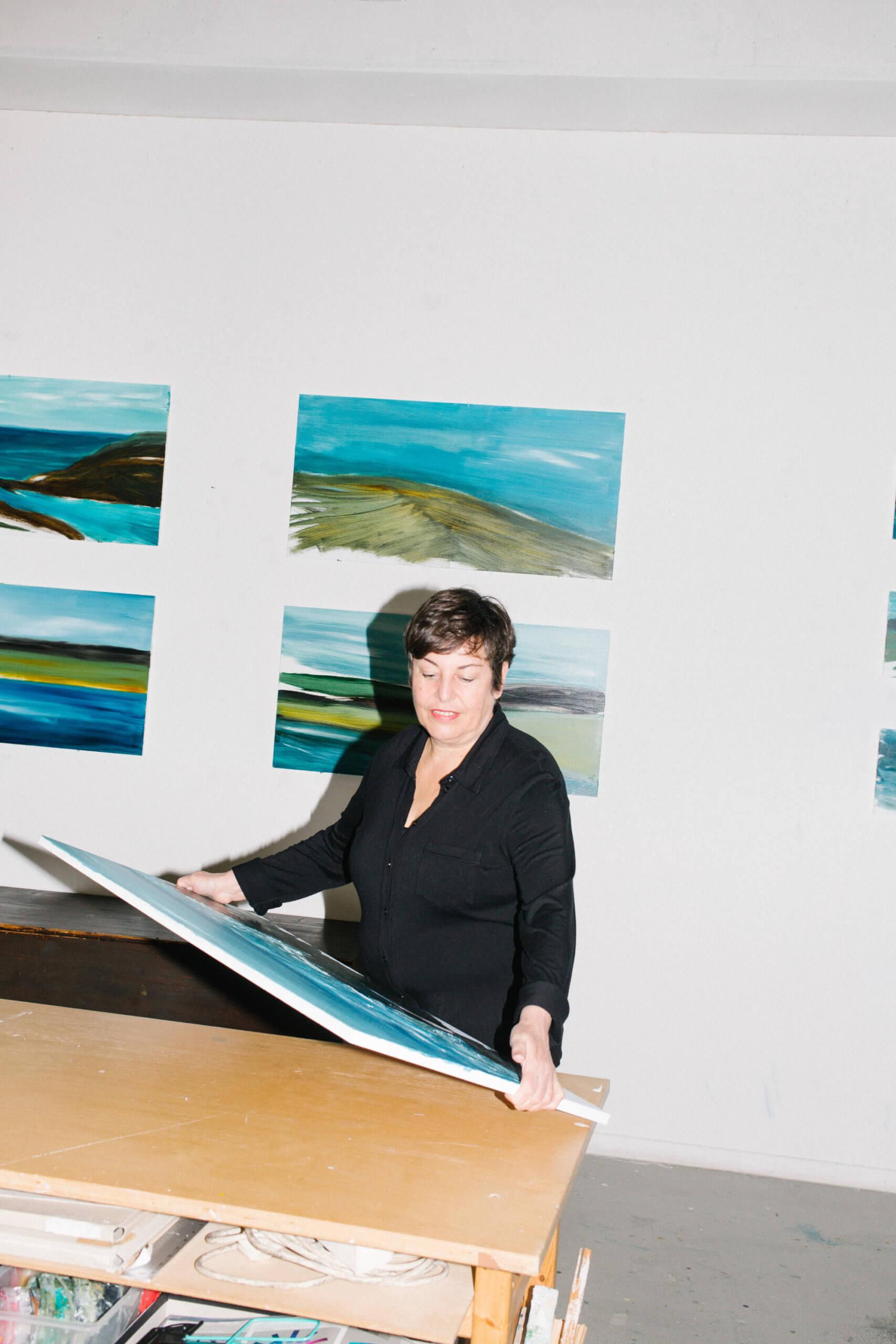 """Man sieht MOnka Humm in Ihrem Atelier, auf ein Bild schauend, welches sie in den Händen hält. Hinter ihr sind Arbeiten aus der Serie """"Landscapes - Places of Longing"""" von 2020 zu sehen."""