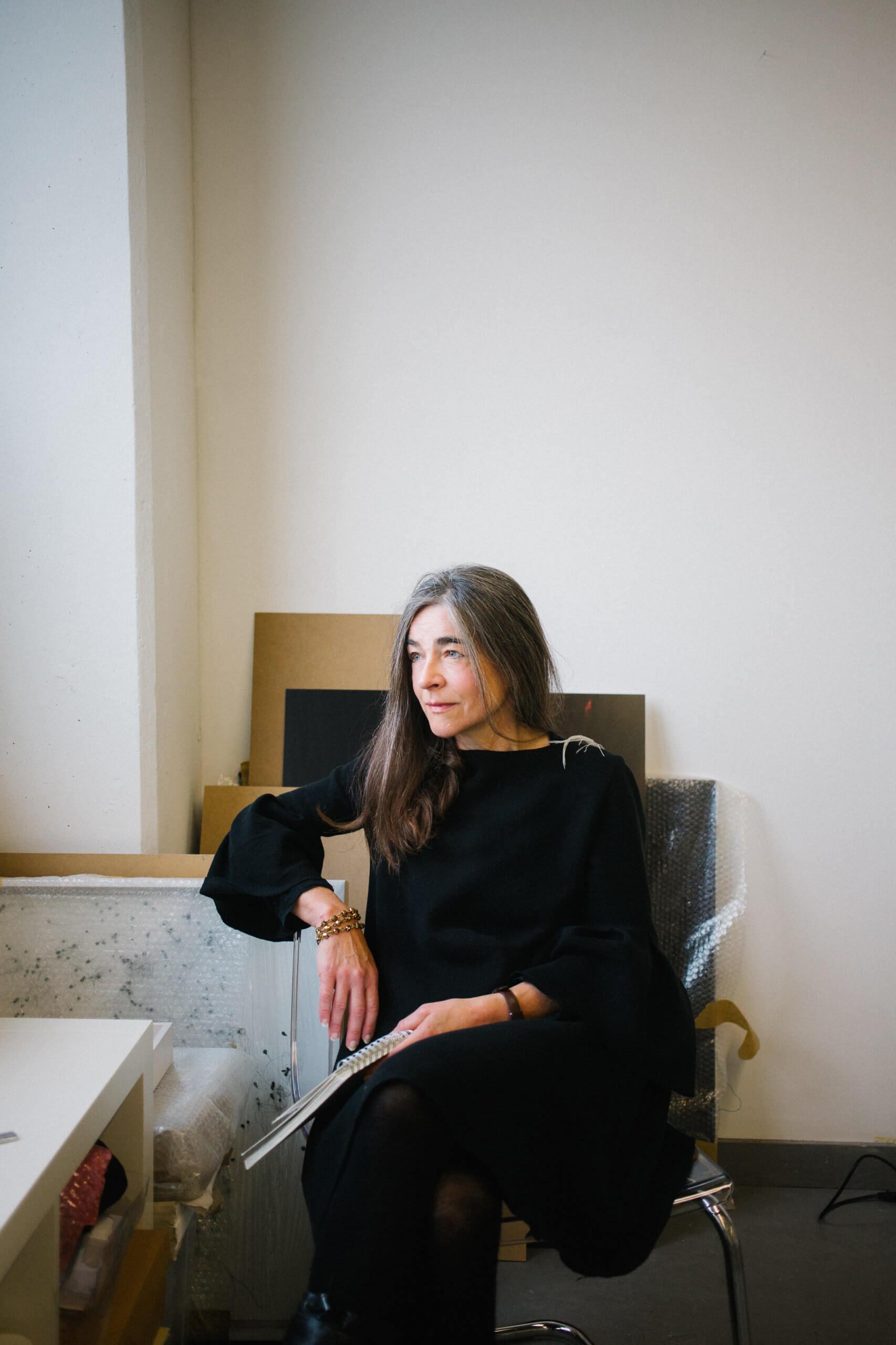Die Künstlerin Patricia Lincke sitzt in ihrem Atelier und schaut aus dem Fesnter