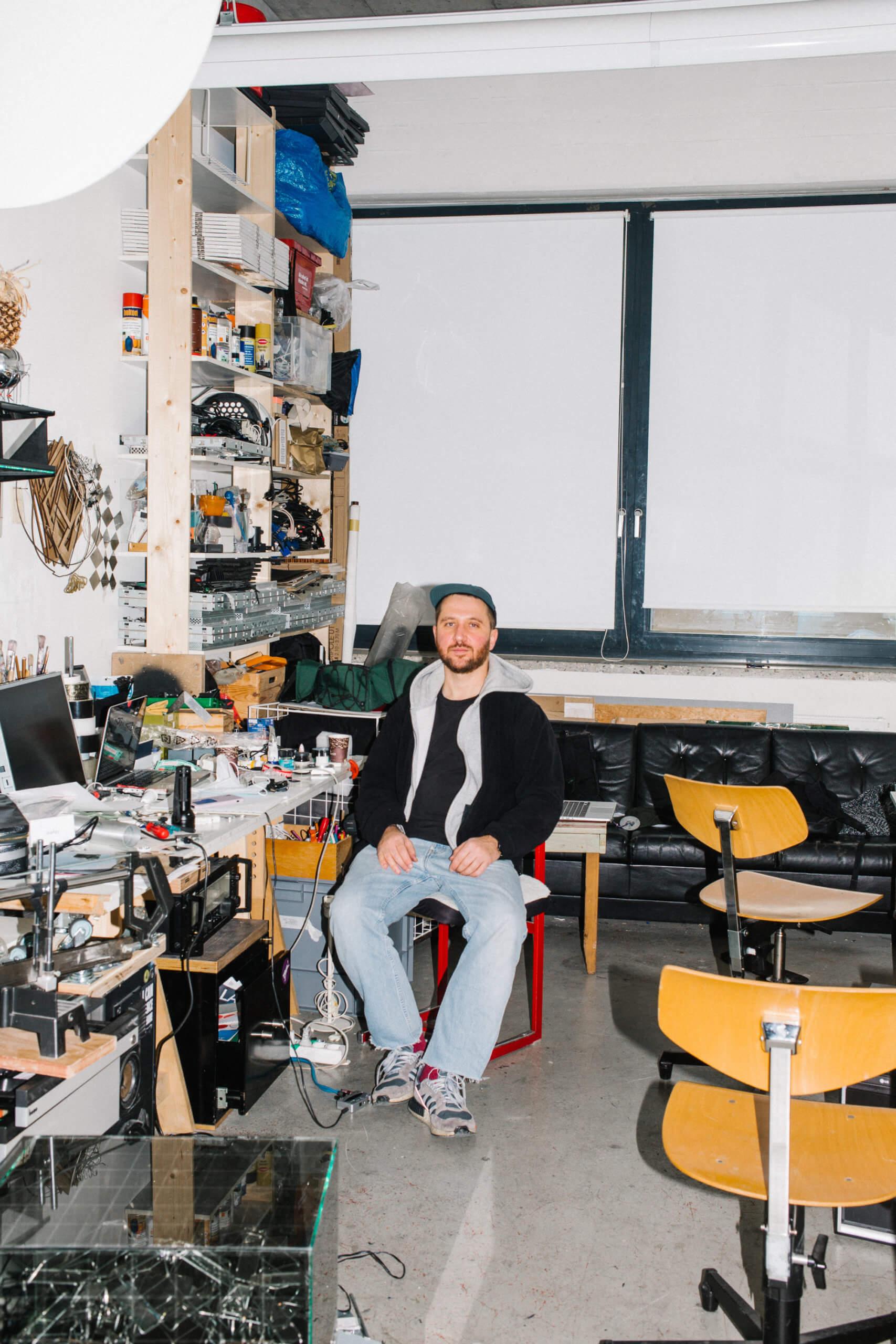Ivan Paskalev sitzt, frontal der Kamera zugewandt, in seinem Atelier.