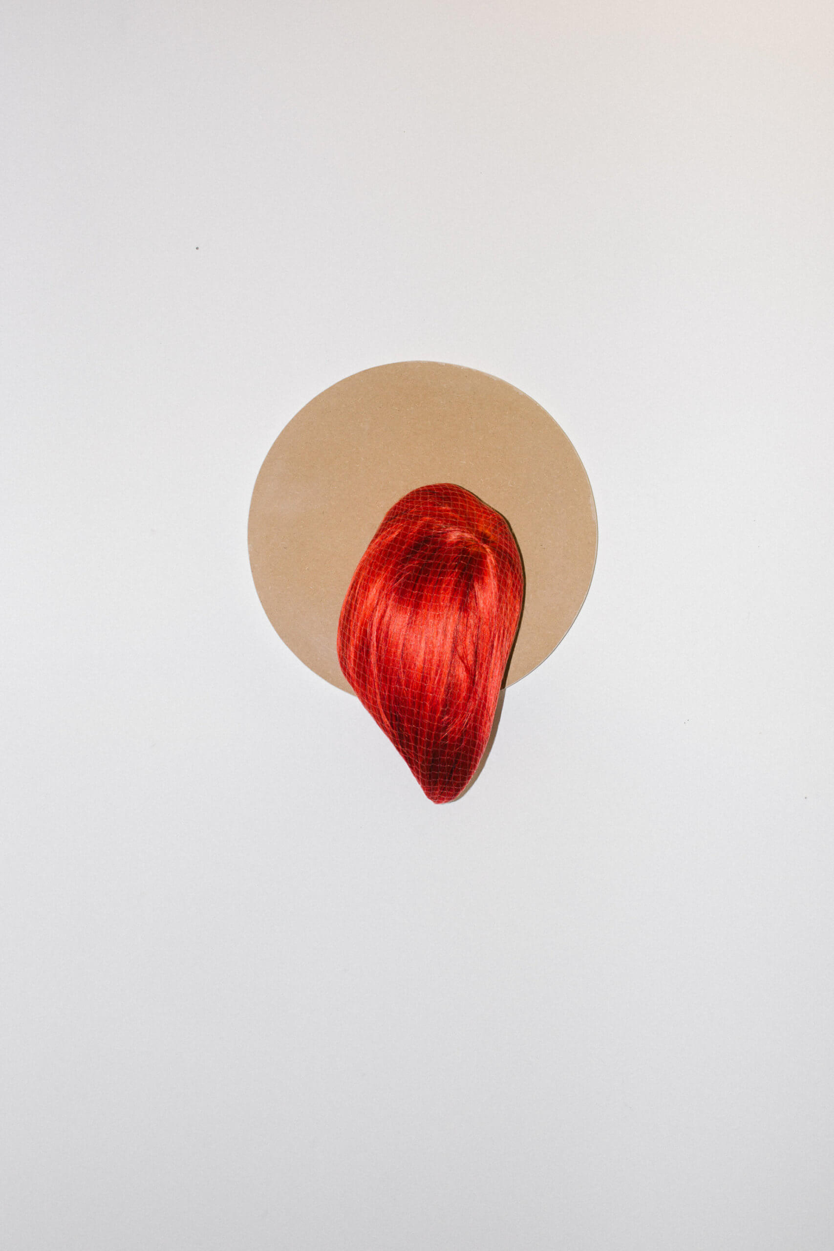 """Die Arbeit aus der Serie """"Burstbilder 2.0"""", von Patricia Linkce, besteht aus einer roten Perücke die an einer braunen, runden Platte befestigt ist, die an der Wand hängt."""