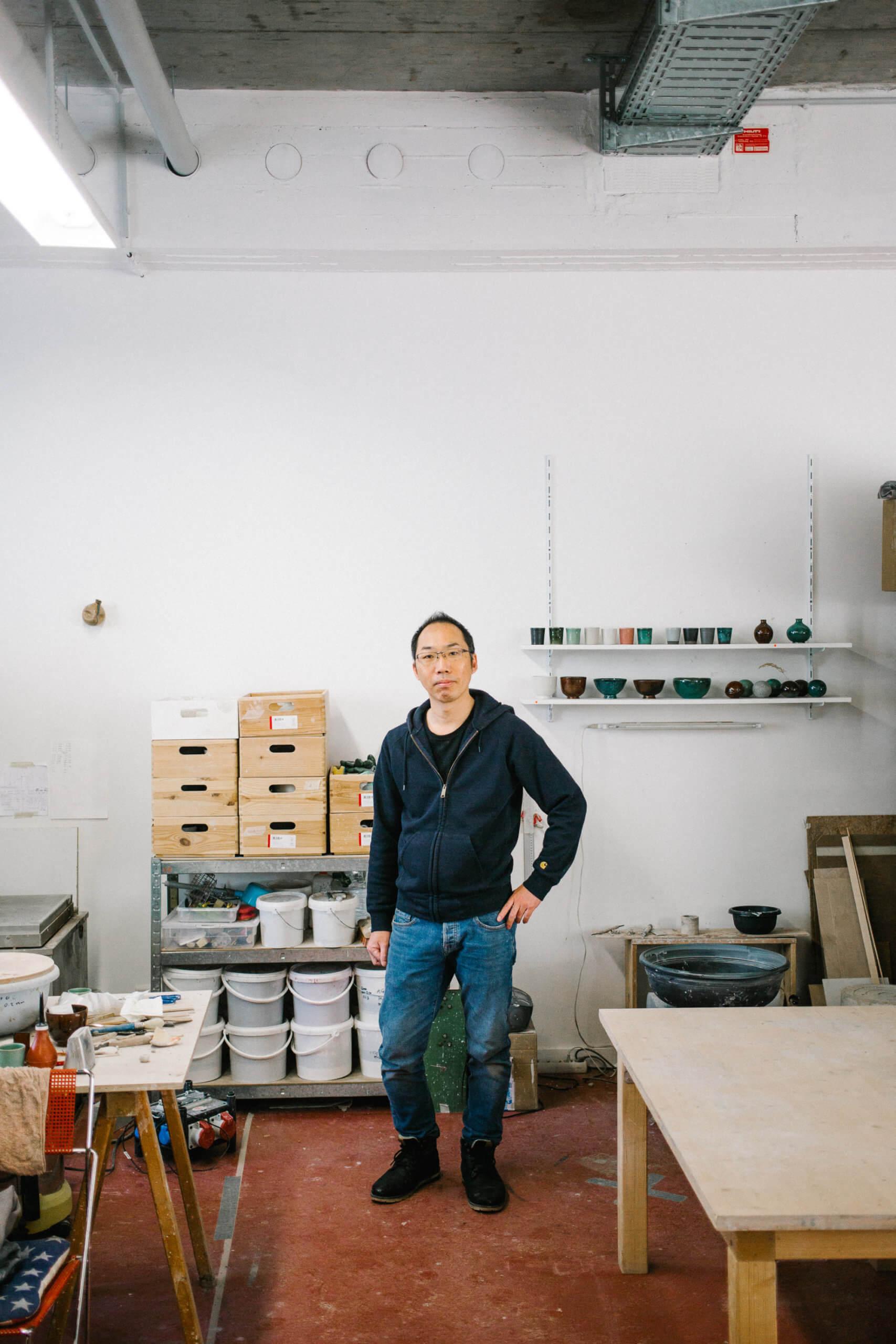 Daisuke Ogura steht frontal in seinem Atelier