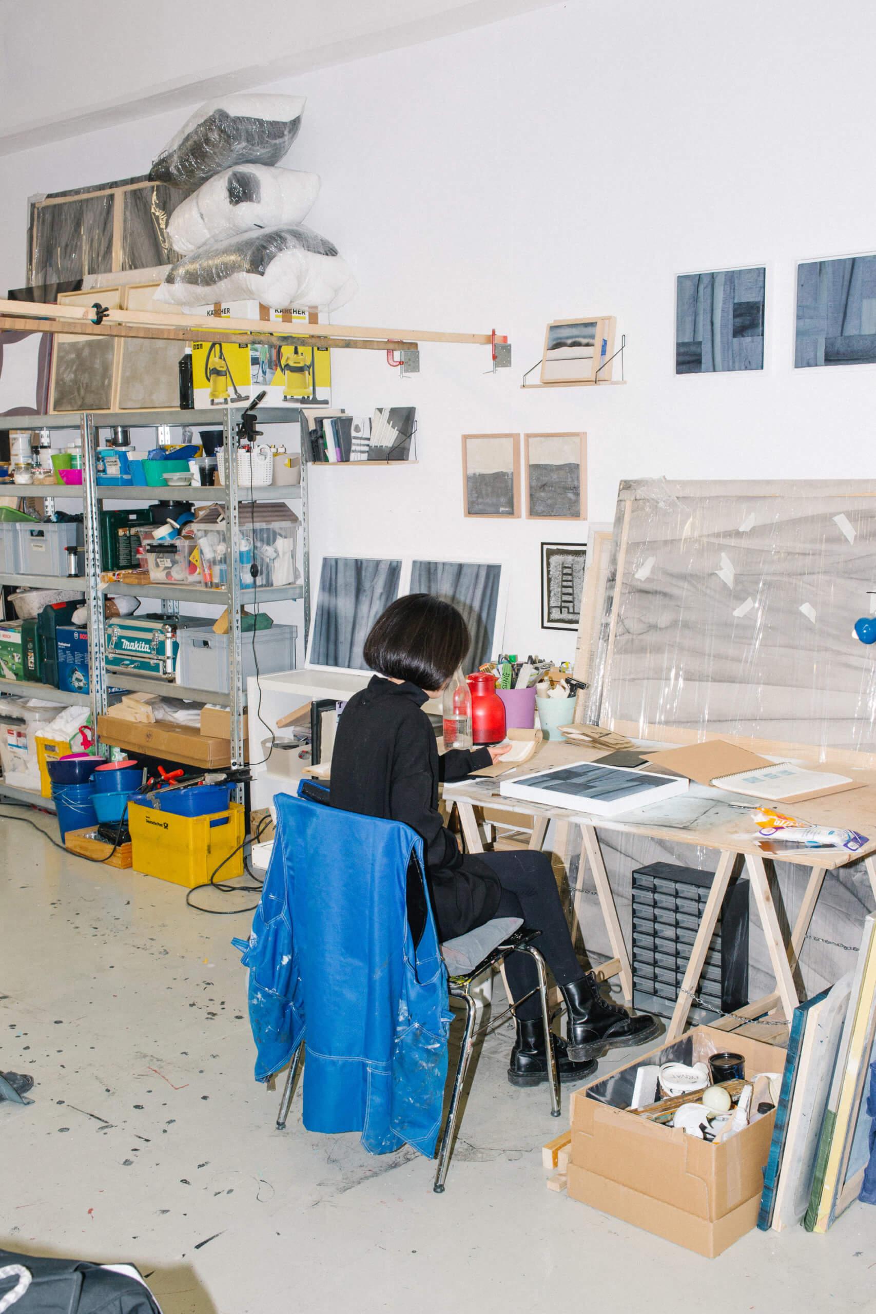 Die Künstlerin Hyun Sung Park ist in der Rückansicht zu sehen, wei sie in ihrem Atelier sitzt und an ihrem Tisch arbeitet