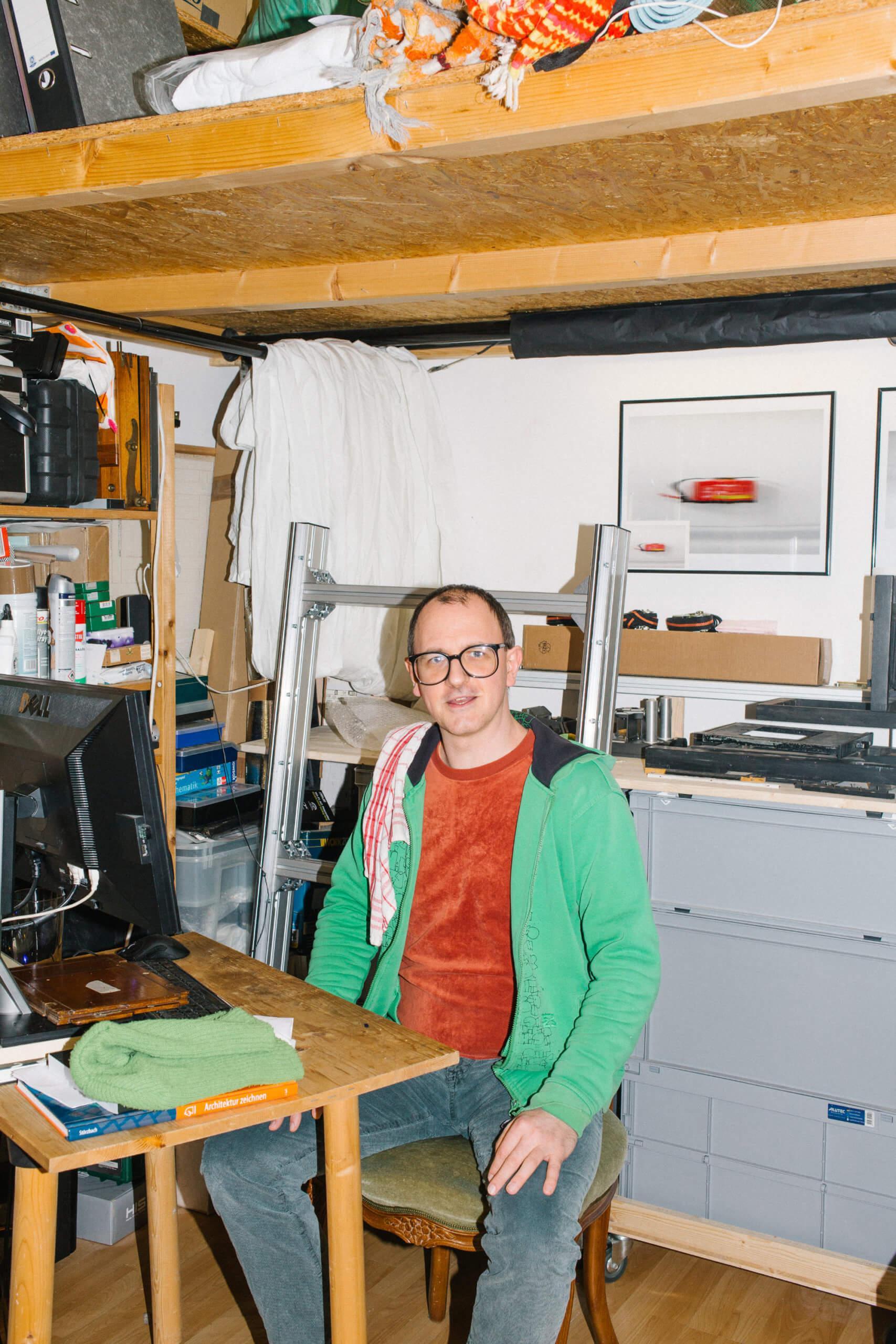 Florian Betz sitzt an seinem Schreibtisch in seinem Atelier