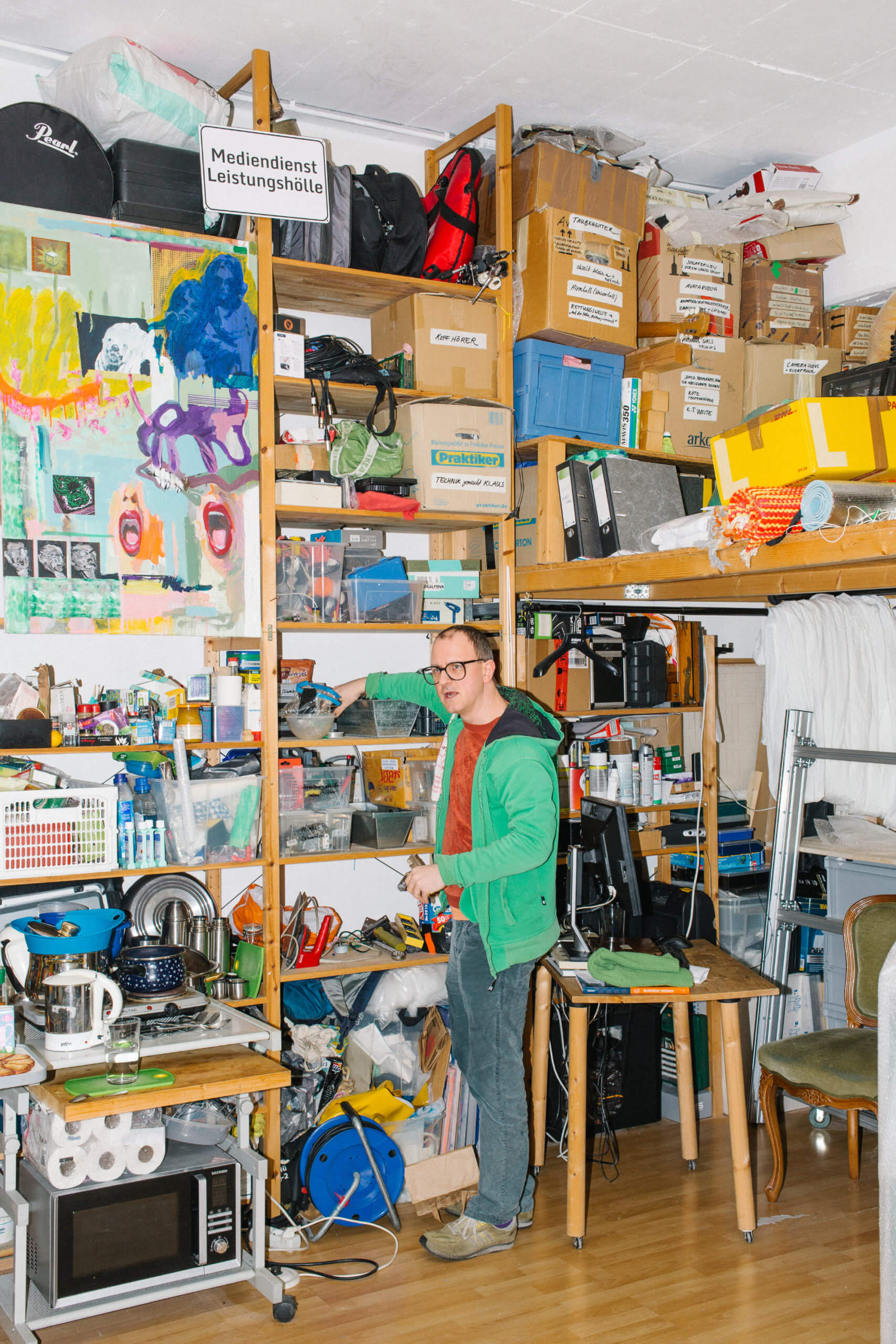 Florian Betz steht angelehnt an einem Regal in seinem Atelier