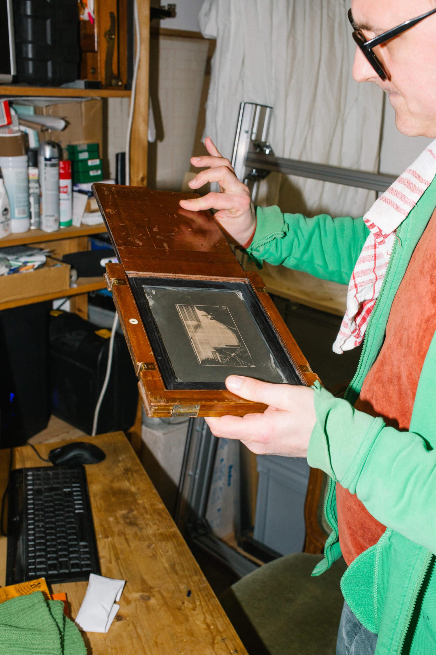 Florian Betz hält ein kleines Kunstwrk in seinen Händen. Es ist ein kleiner Siebträger für Siebdruck in einer Holzschachtel
