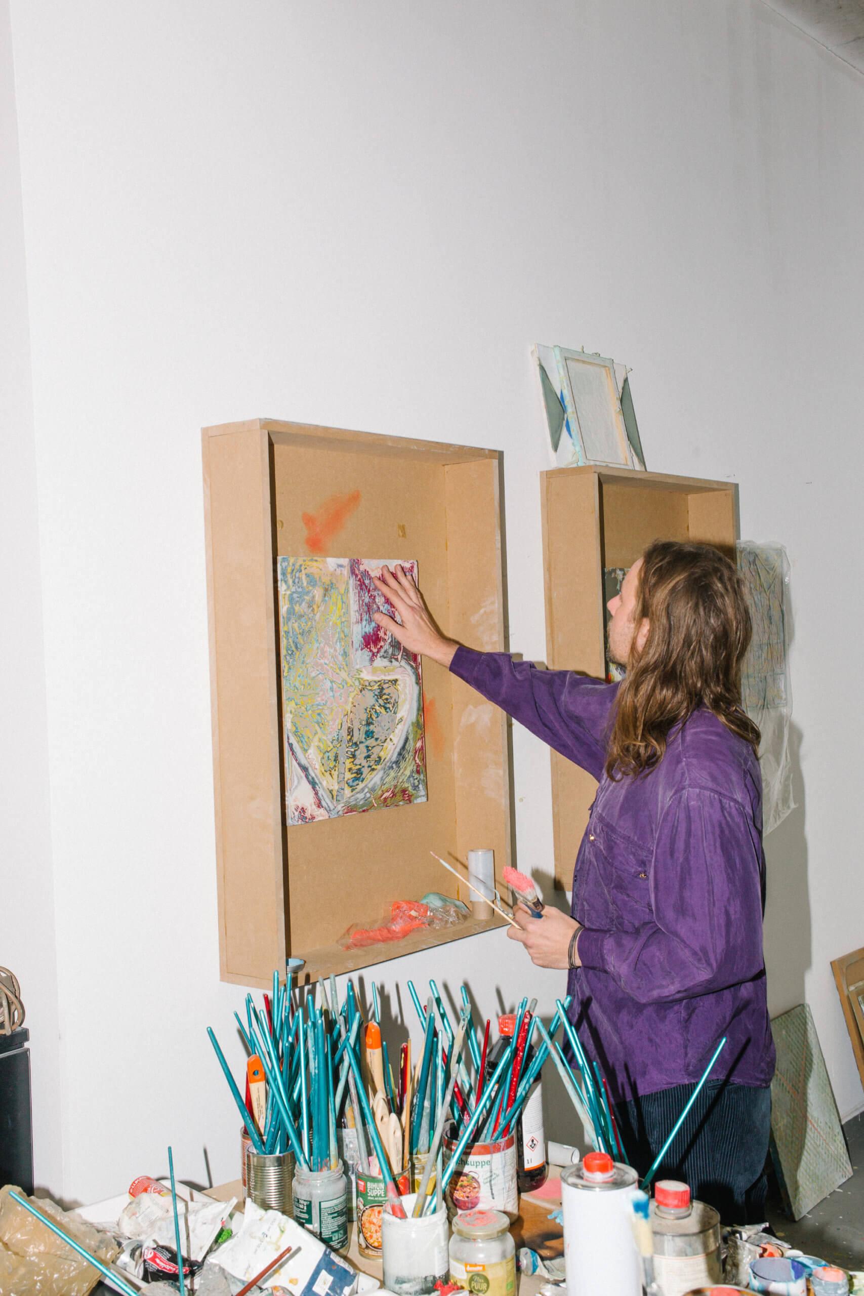 Raik Gupin steht in Rückansicht vor dem Fotografen und bearbeitet ein Werk, welches an der Wand hängt