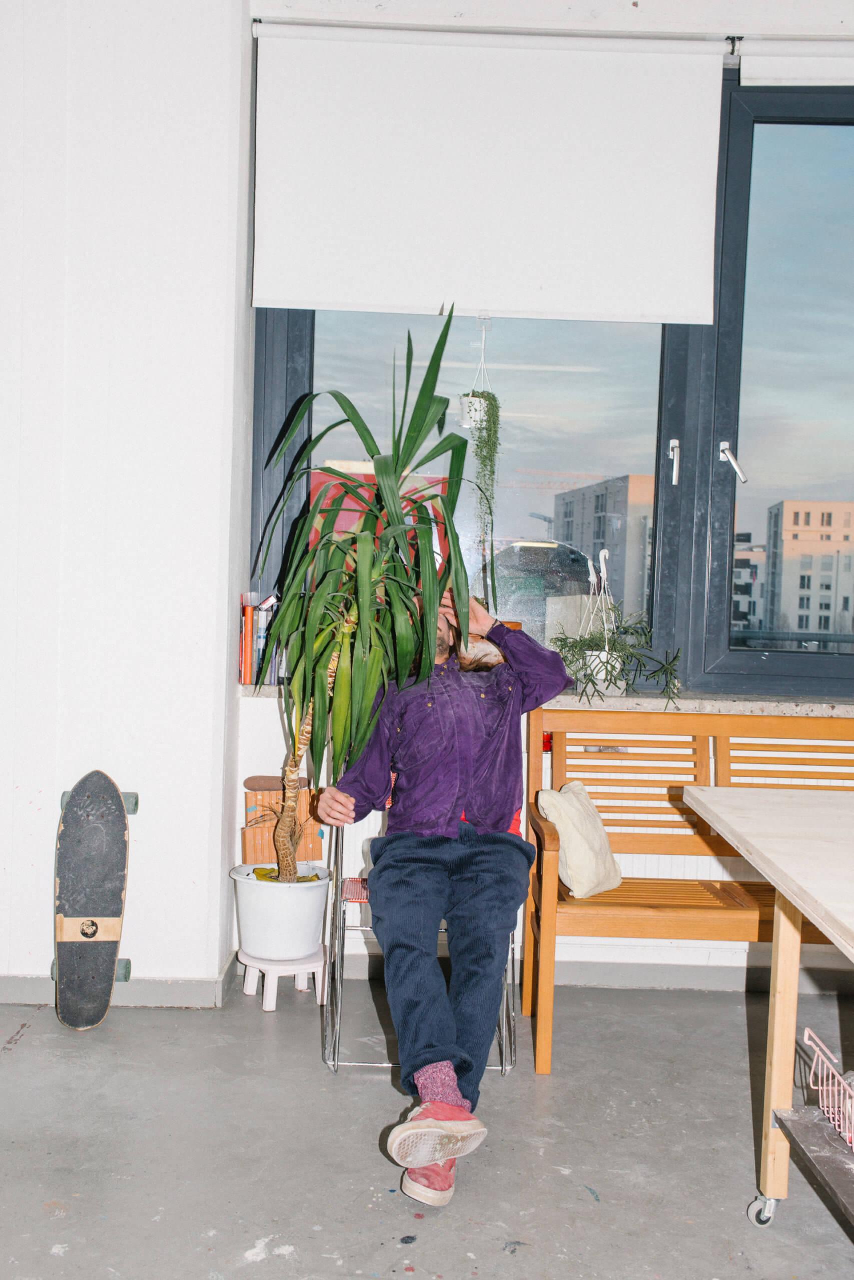 Raik Gupin sitzt auf einem Stuhl vor dem Fenster und versteckt sein Gesicht hinter einer Palme.