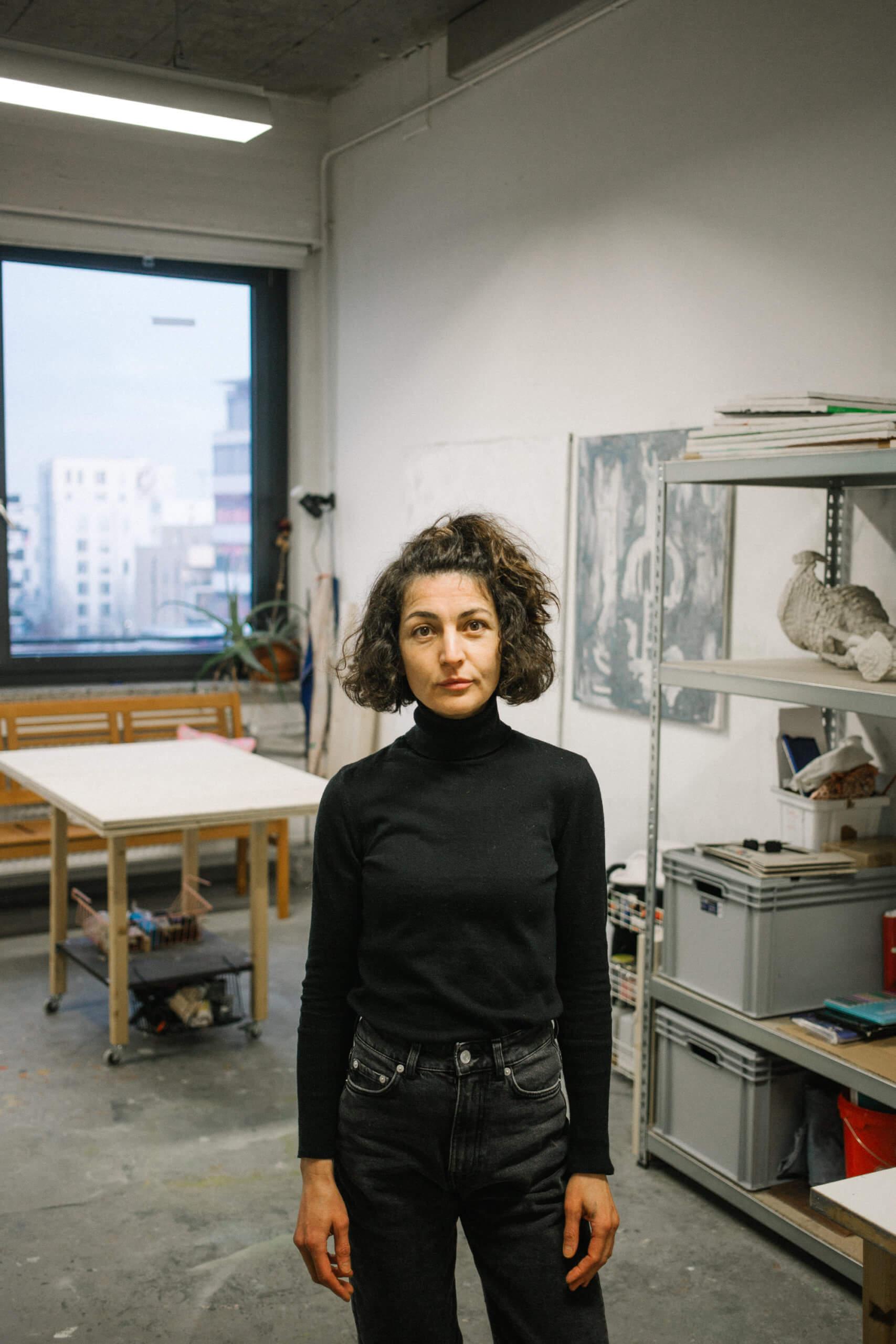 Die Künstlerin Gülcan Turna steht in ihrem Atelier und blickt frontal in die Kamera.