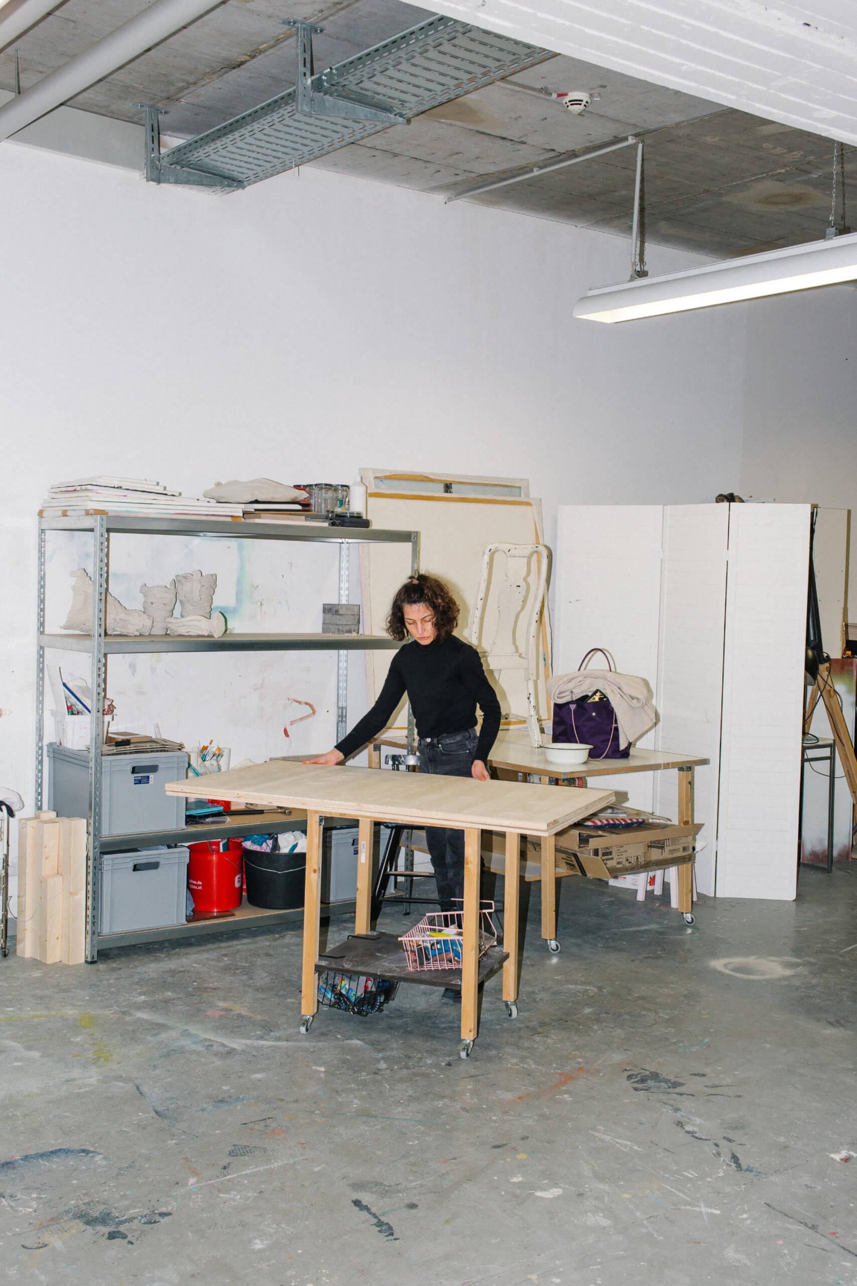 Die Künstlerin Gülcan Turna steht in ihrem Atleir über ihren Tisch gebugt und legt Fotos ihrer Abreiten zurecht.