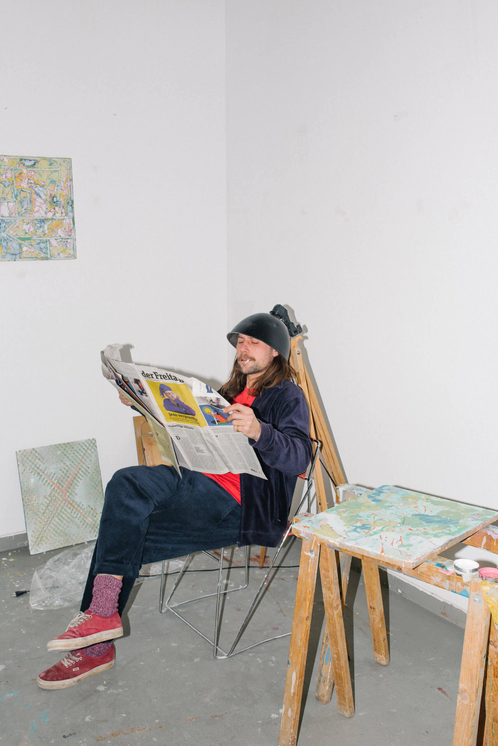 Raik Gupin sitzt Zeitung lesend in einem Stuhl, und hat einen Lampenschirm auf dem Kopf.