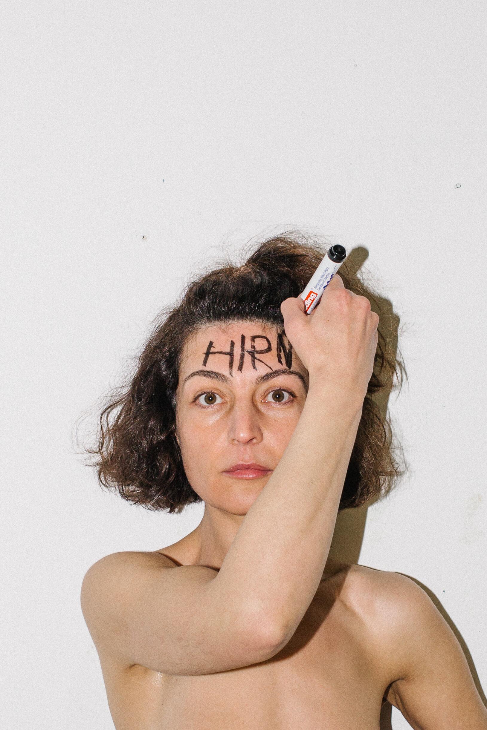 Die Künstlerin Gülcan Turna steht frontal zur Kamera, nackt, und Schreibt sich das Wort Hirn auf die Stirn.