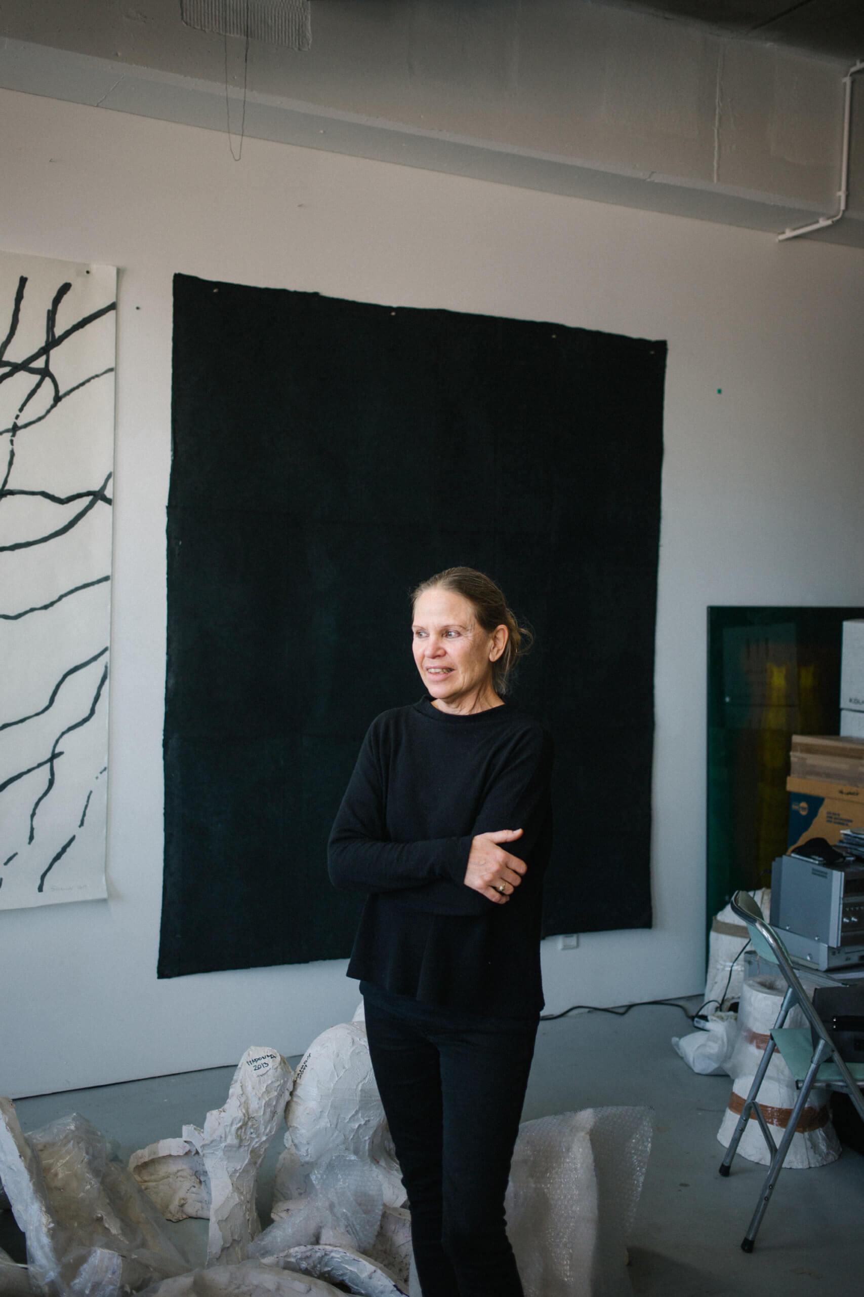 Silvia Schreiber steht in ihrem Atelier vor einer schwarzen Leinwand