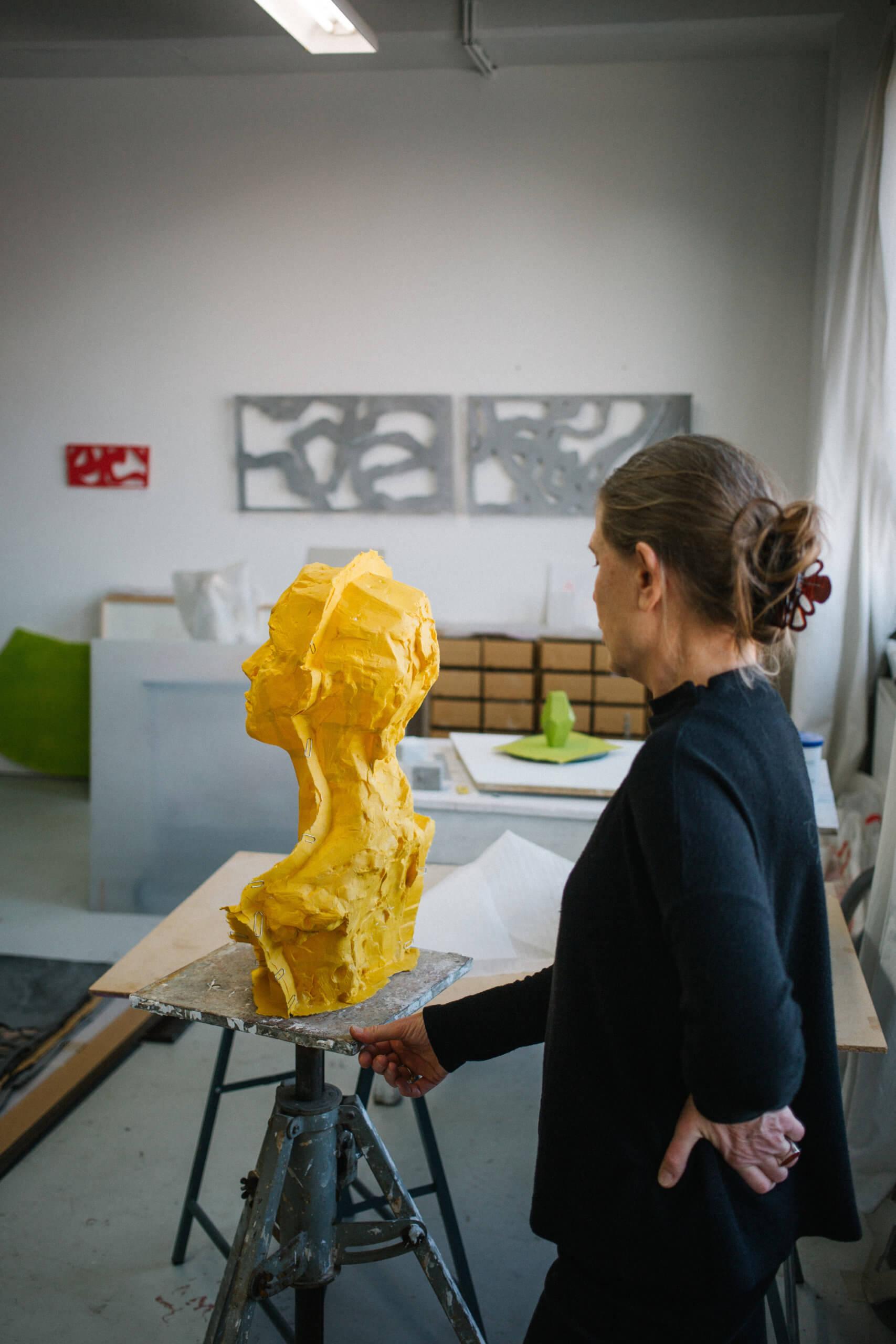 Slivia Schreiber steht in Rückansicht vor einem gelben Papierkopf