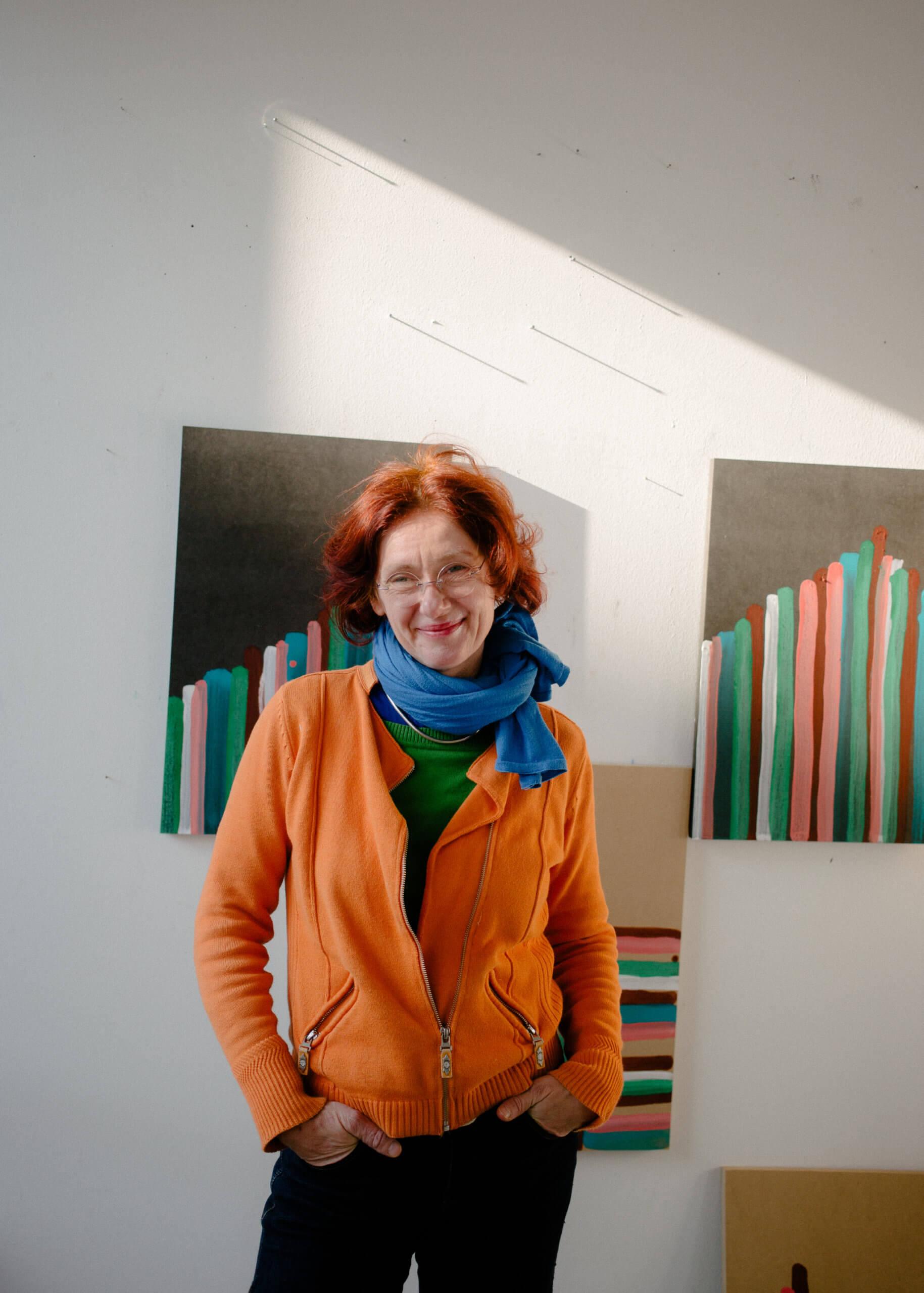 Ein Portrait von Annegret Hoch in ihrem Atelier. Sie steht vor einer weißen Wand an denen unfertige Arbeiten von ihr hängen.