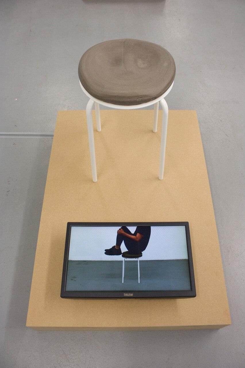"""Es ist das Werk """"Eine Scheibe"""" von Daisuke Ogura zu sehen. EIn Hocker mit einer Keramikscheibe ist auf einem flachen MDF-Sockel zu sehen. vor dem Hocker ist ein kleiner Bildschiorm auf dem der Künstler sich auf diese Keramikscheibe setzt."""
