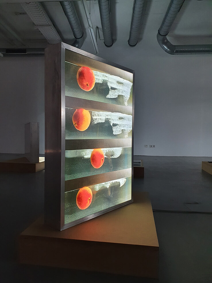 """die Arbeit """"Luft Fracht Frucht Eis leuchten"""" von Stephanie movall steht auf einem MDF Sockel in einer dunkeln Halle."""
