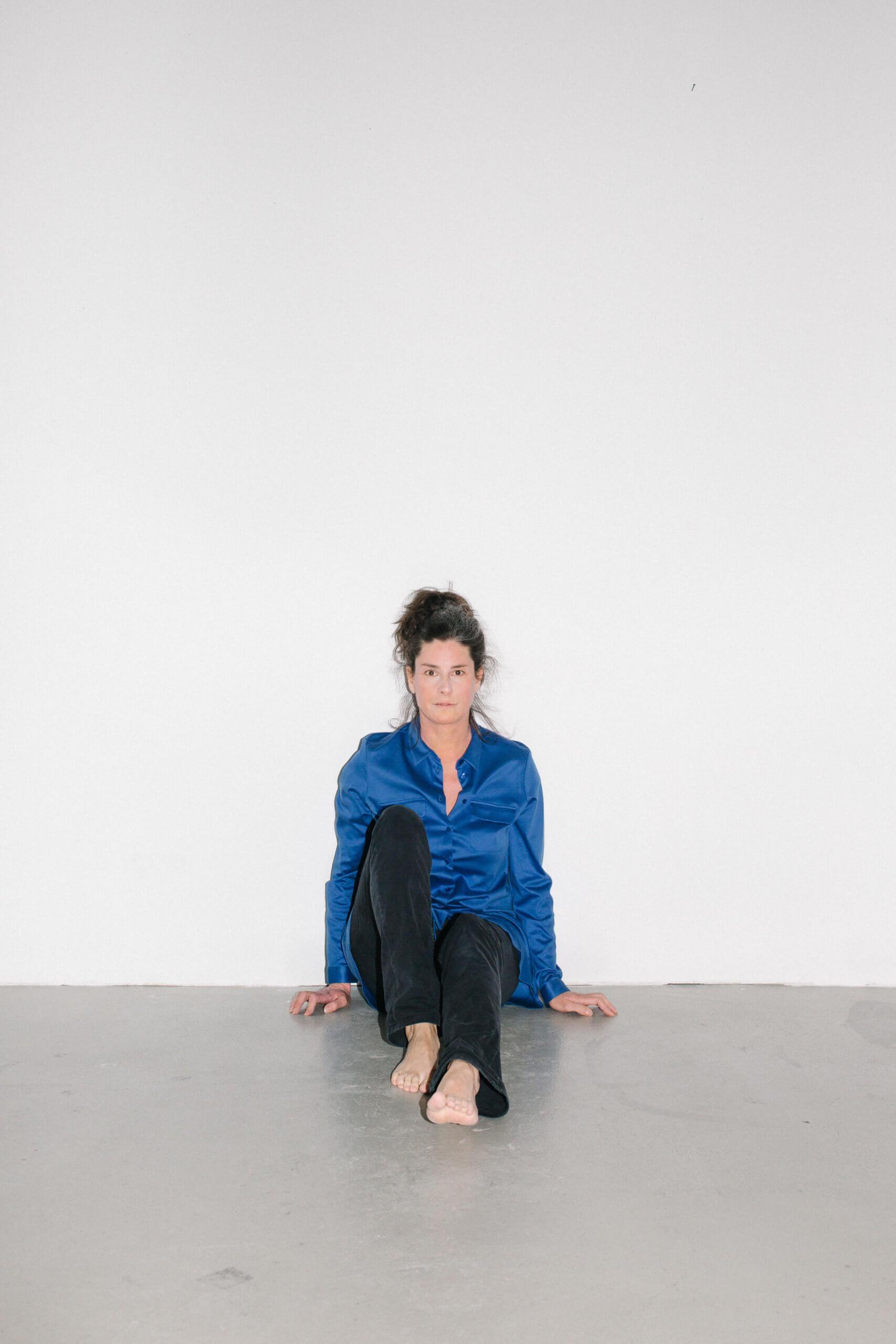 Stephanie movall sitzt auf dem Boden, an eine weiße Wand gelehnt. Sie schaut direkt in die Kamera.